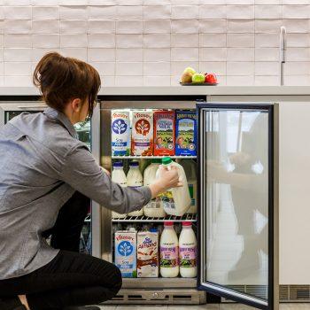 Valet restocking milk supplies in the workplace fridge.