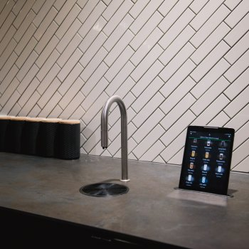 A TopBrewer coffee machine and iPad against a dark counter and white tiled walls
