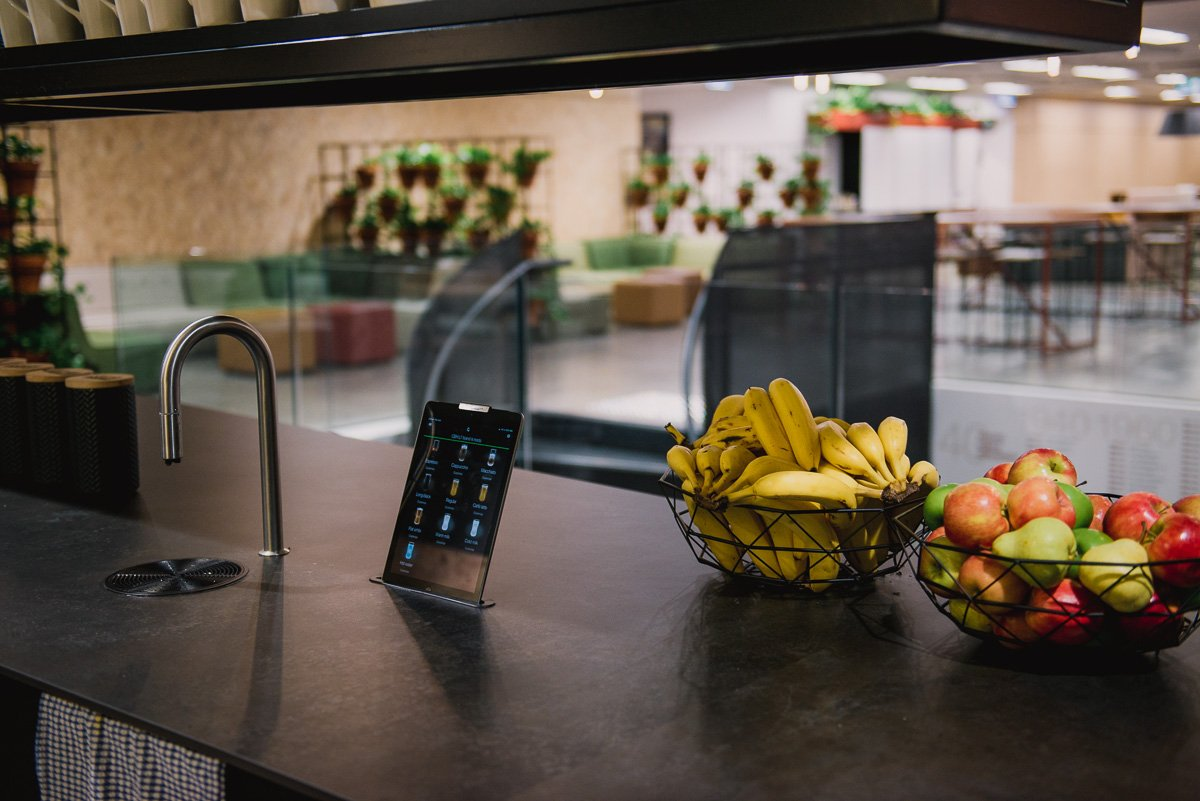 TopBrewer and iPad next to bowls of fruit on a dark counter in an office kitchen hub